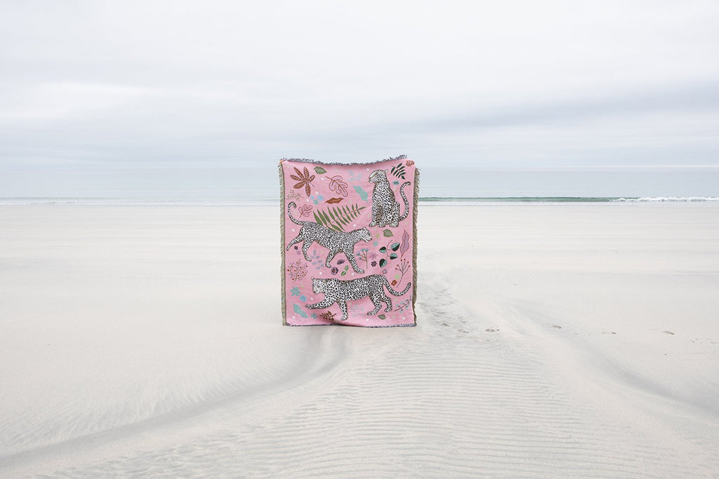 Snow Leopard blanket held up on a beach