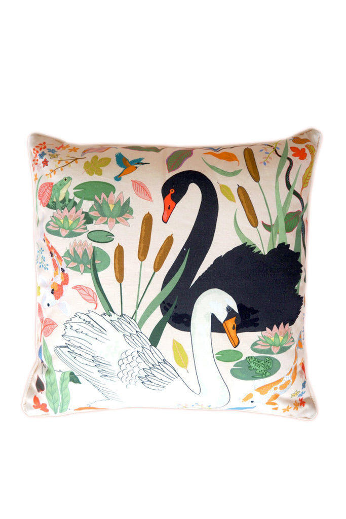Karen Mabon Swan Lake Cushion with cream base featuring one black and one white swan, among reeds, lily pads and leaves.