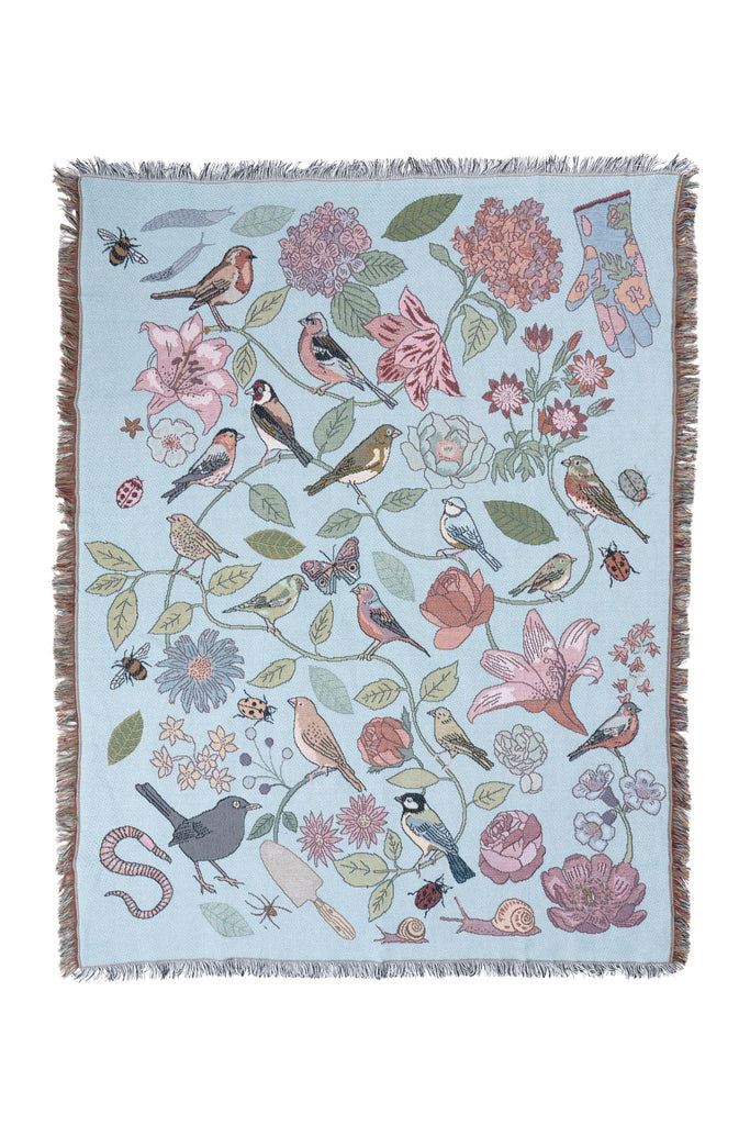 Product photo of woven blanket by Karen Mabon, featuring illustrations of British birds, flowers, insects, gardening gloves and tools.