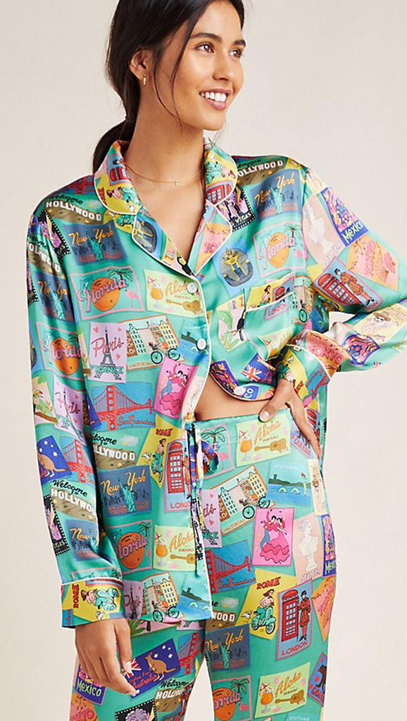 Wish You Were Here printed pajama silk shirt, with blue background and an array of vintage postcards from different countries.