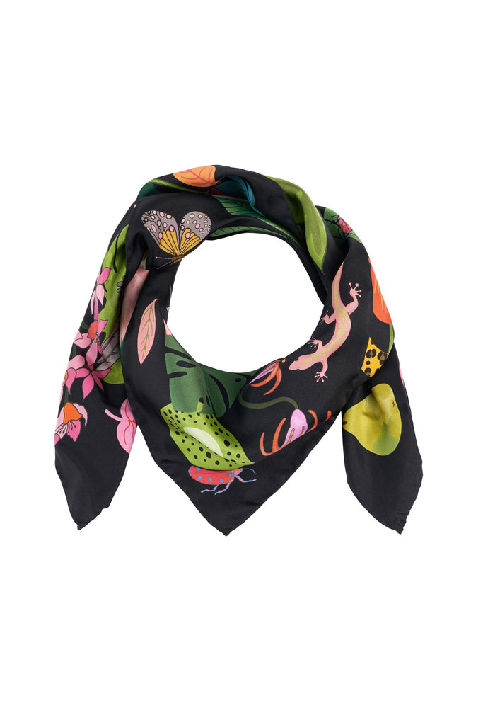 Rainforest silk scarf rolled up with a butterfly and lizard slightly visible.