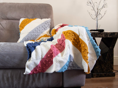 Winter Brights Blanket and Cushion by Zoë Potrac in Deramores Studio DK