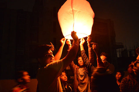 Peeyush lighting sky lanterns with children
