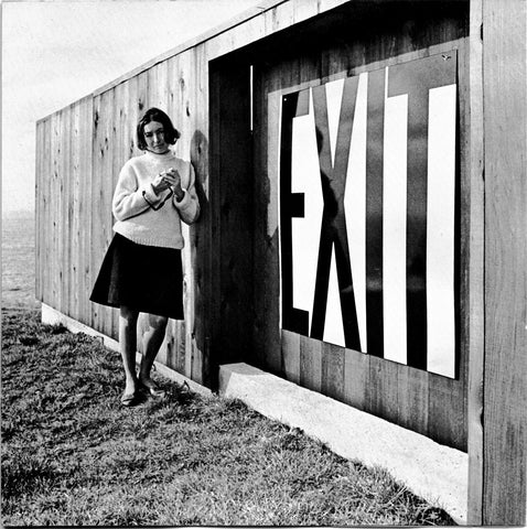 Barbara Stauffacher Solomon beside an enamel exit sign at Lawrence Halprin's house at The Sea Ranch.