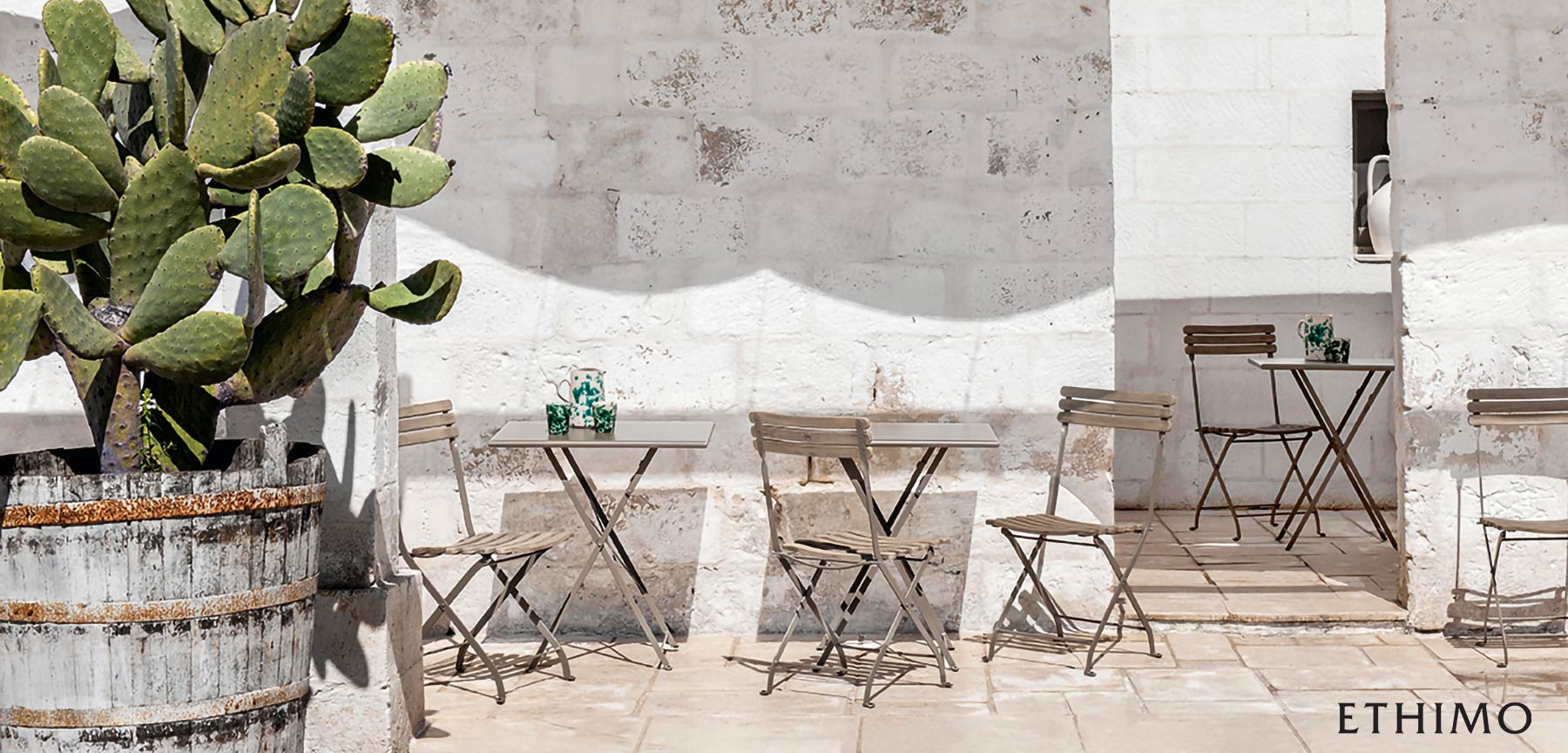 Ethimo Flower Folding Metal Bistro Dining Tables on outdoor patio