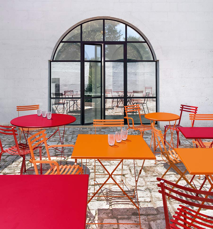 Ethimo colorful metal folding bistro tables and chairs on outdoor patio
