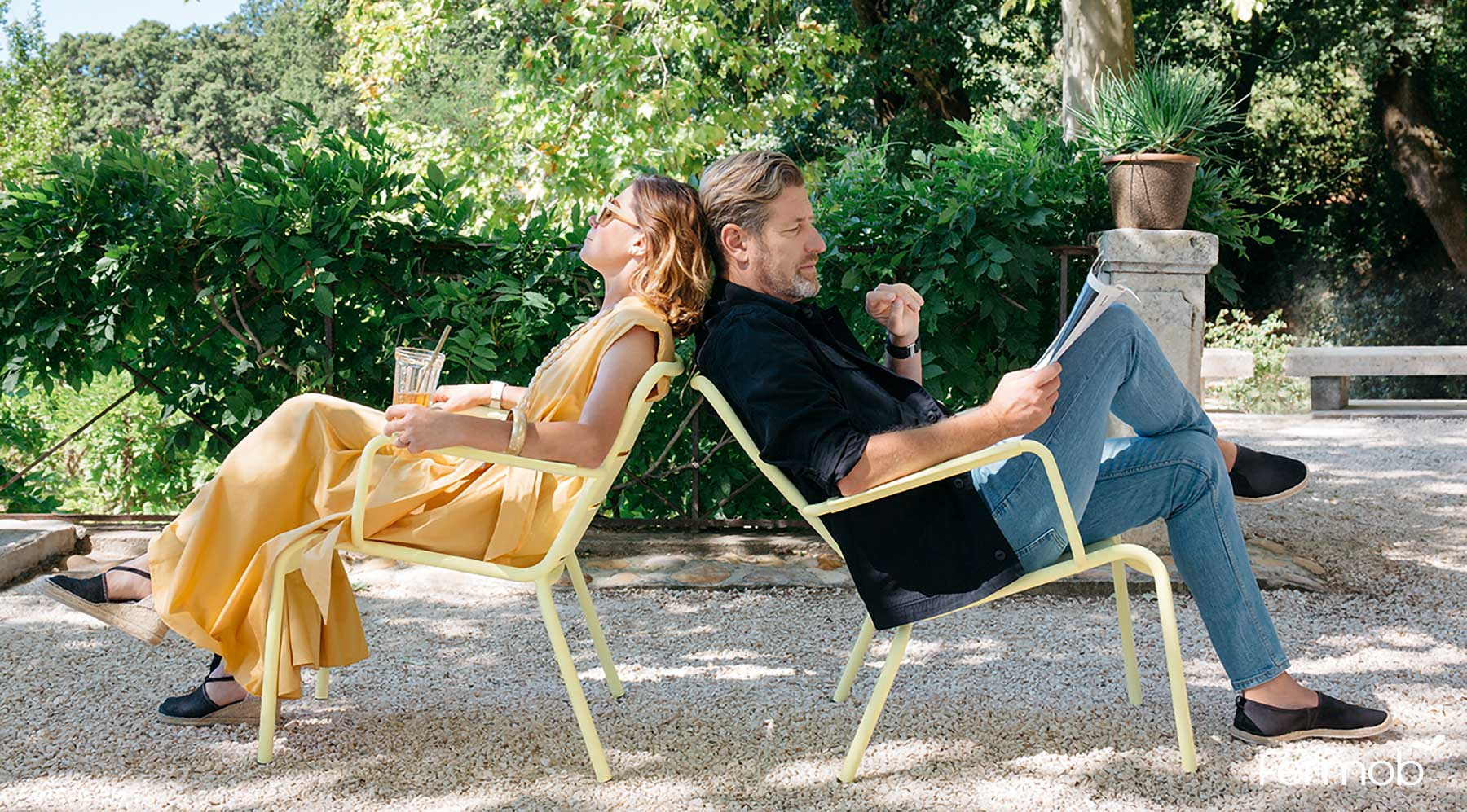Fermob Luxembourg Lounge Armchairs with man and woman seated in outdoor garden space