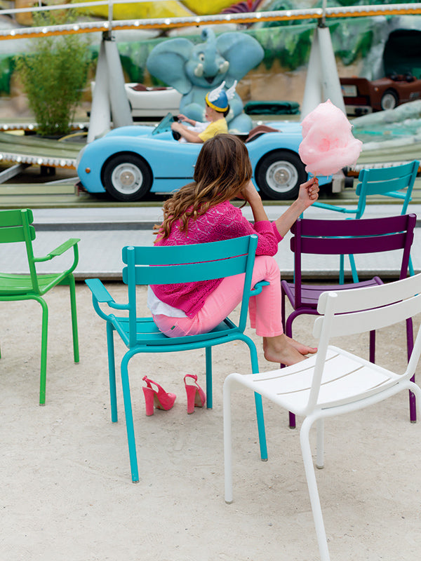 child sitting on colorful fermob chairs