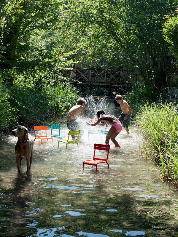 children playing in creek with colorful fermob chairs