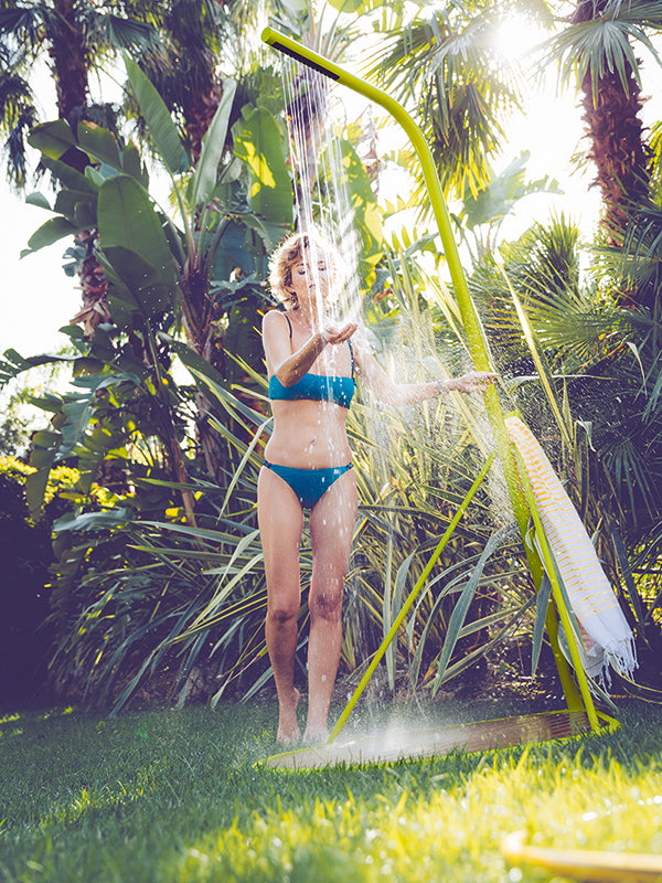 female-model-using-fermob-pasaia-shower-outside-sunny-day
