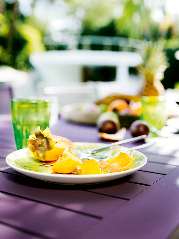 plate with fruit on purple table outside