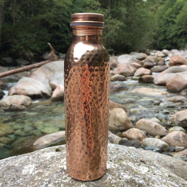 Copper H2O hammered copper water bottle placed on a smooth rock near a river