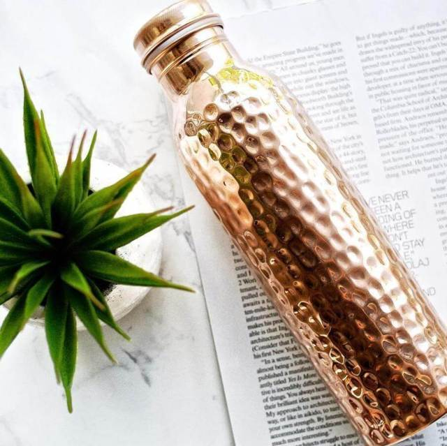 Copper H2O hammered copper water bottle placed on an open magazine