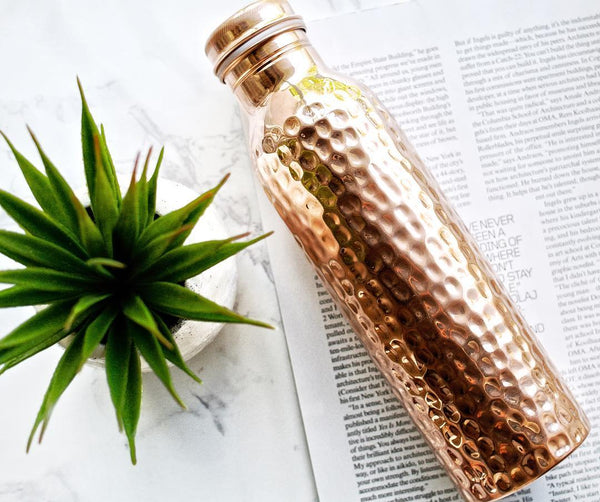 Copper H2O copper hammered water placed on a magazine beside plant