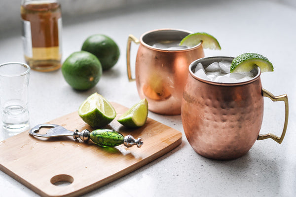 two Moscow Muled copper mugs filled with liquid ice lime wedges