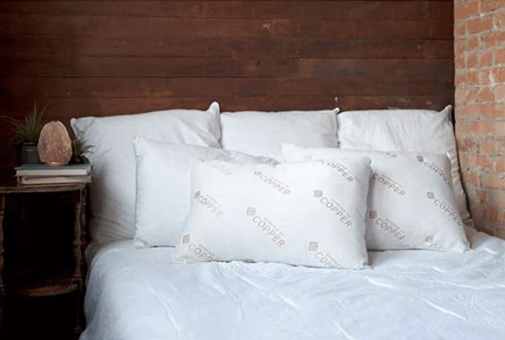 two Essence of Copper Pillow surrounded with larger white pillows placed on a single white duvet covered bed
