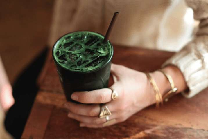 hand wearing gold rings resting on table holding green drink