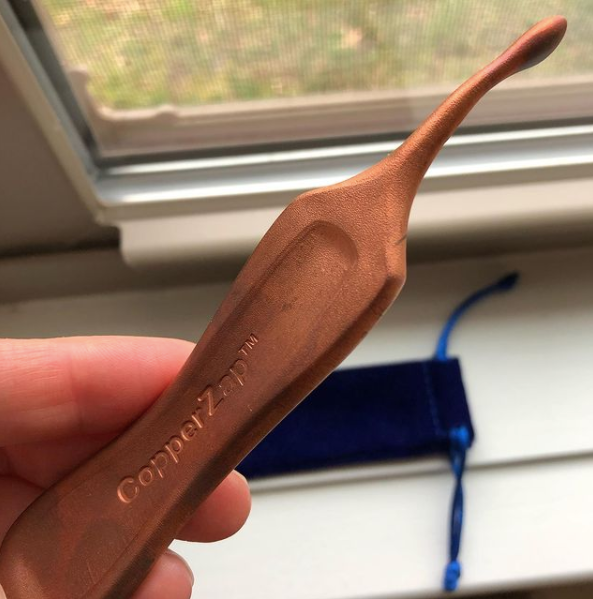 hand holding copper zap by a window
