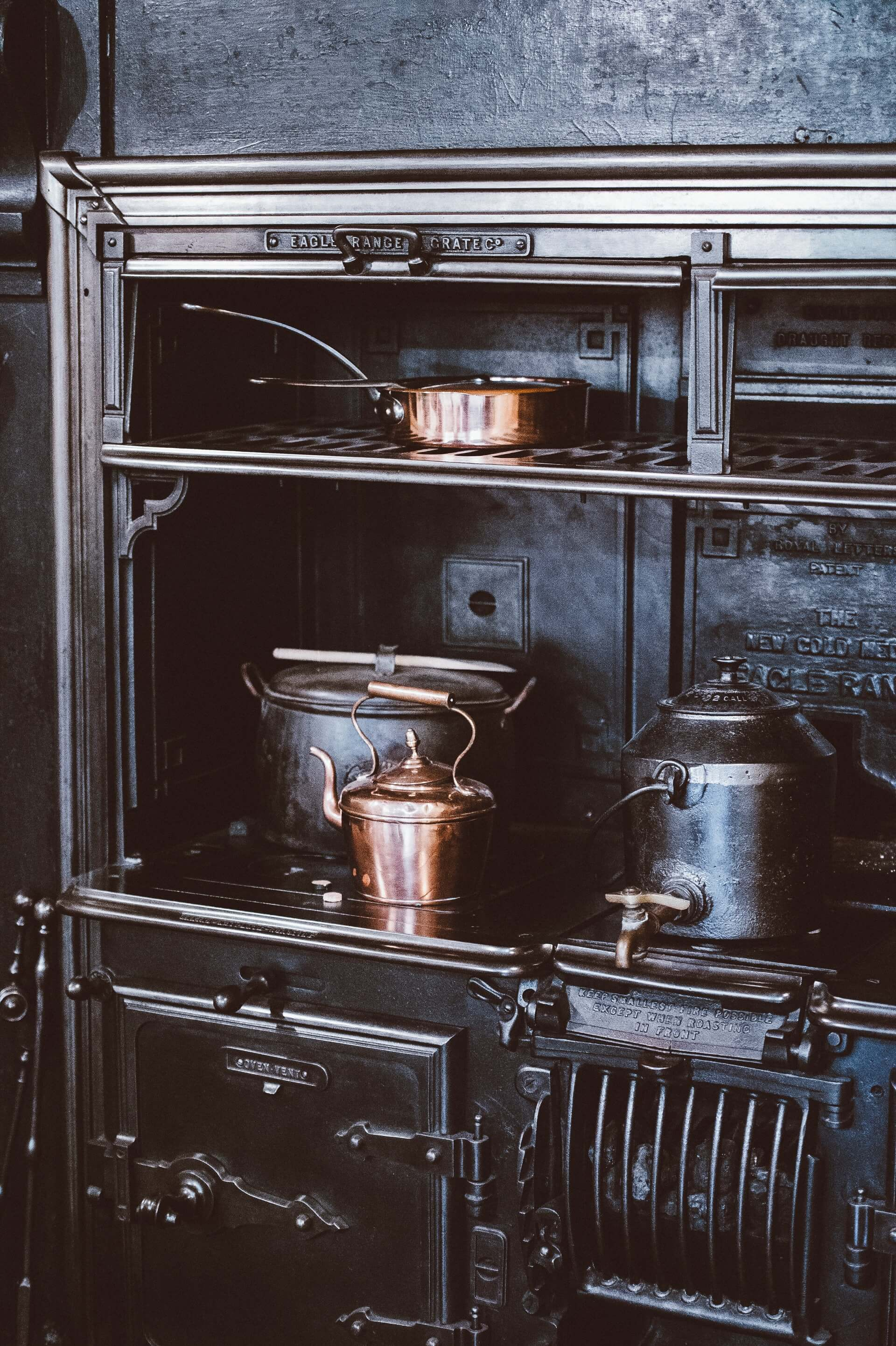 pots and copper kettle and pans placed on a stainless steel stove