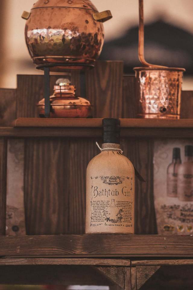 copper items placed on wooden shelf Bathtub Gin bottle on wooden surface