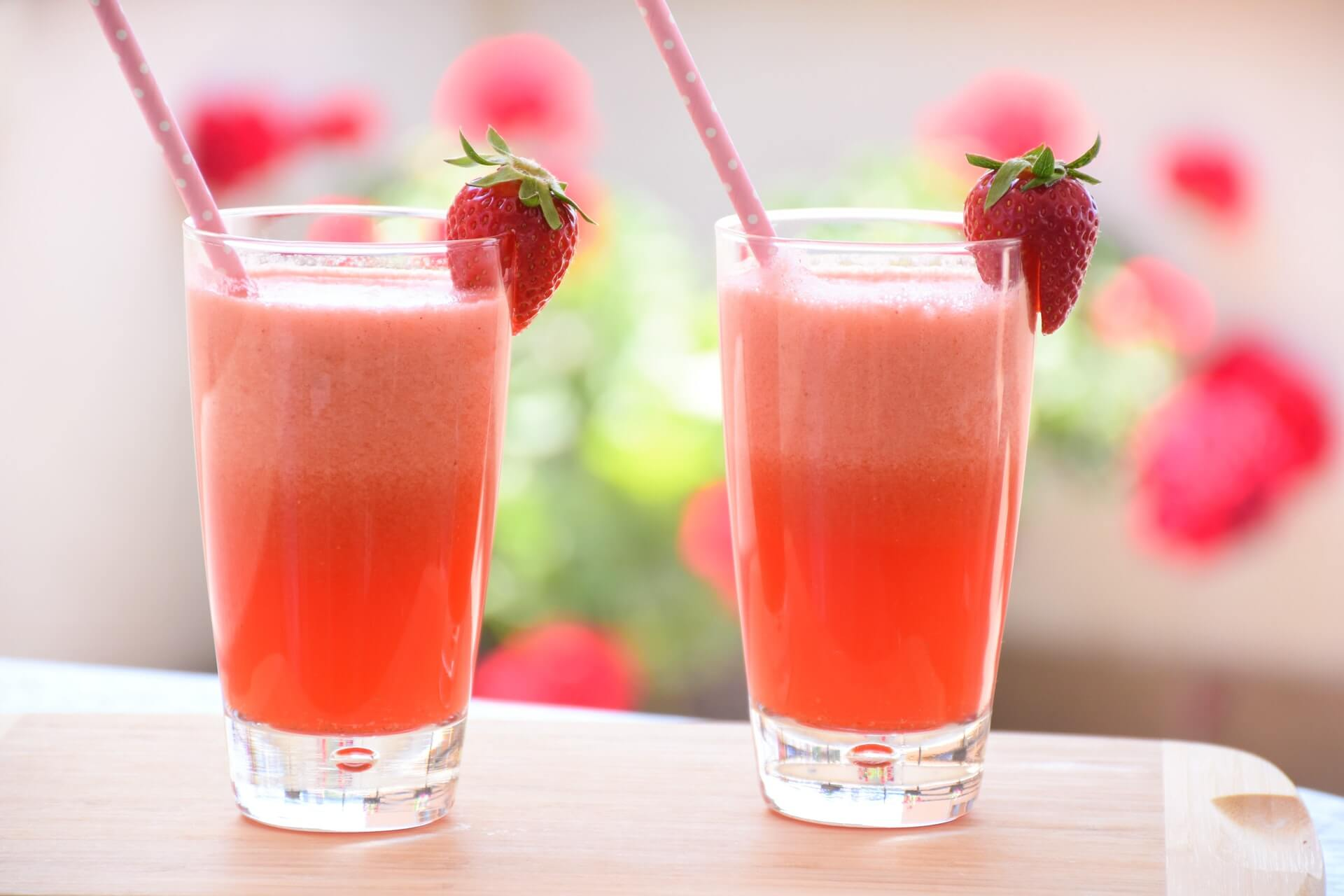 two glasses containing pink liquid straw and strawberries on the rim