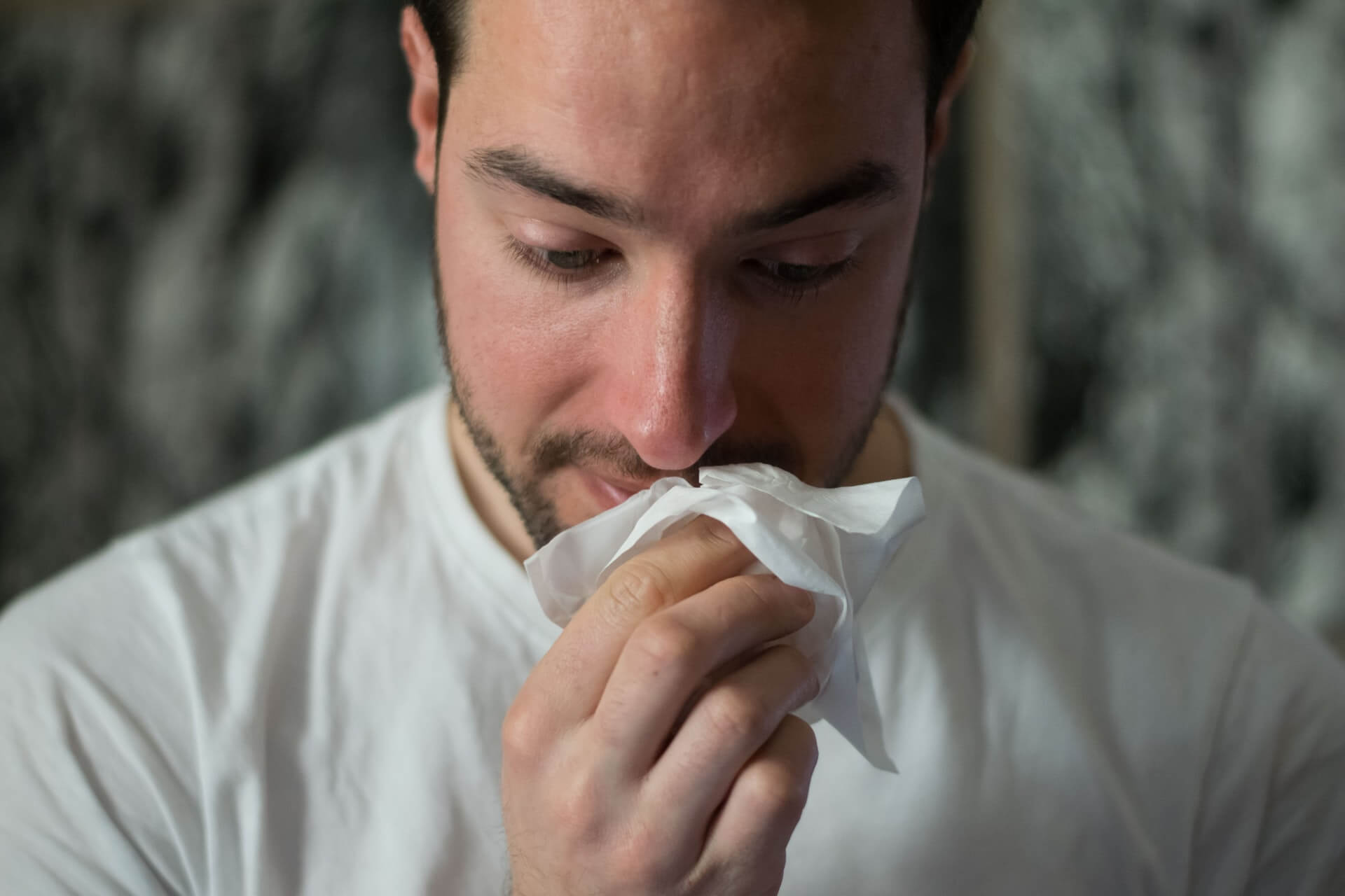 man wearing white shirt wiping nose with tissue