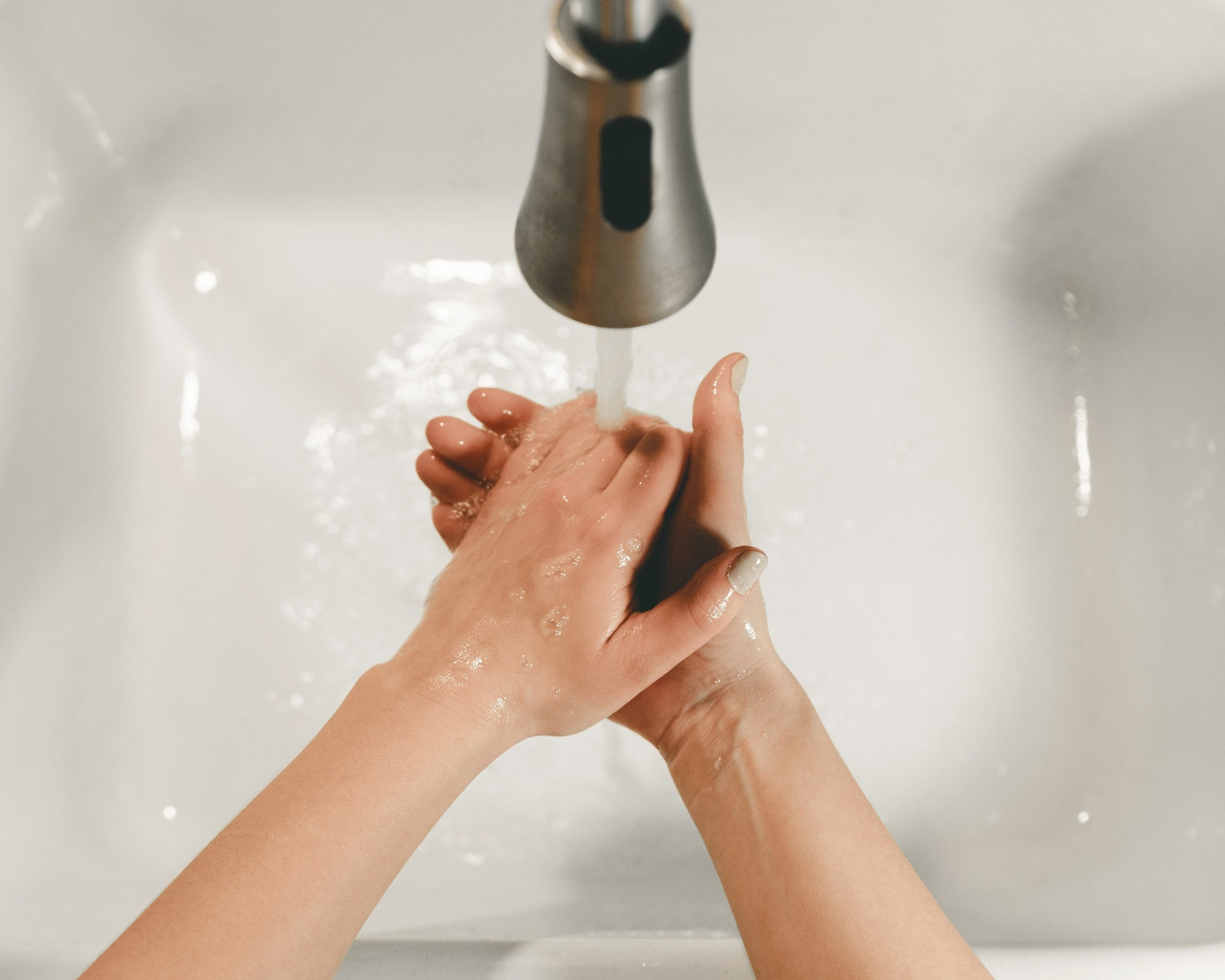 pair of hands washing under running faucet white sink