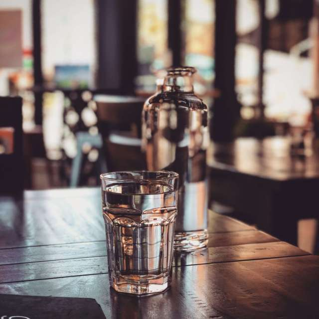 glass of water and bottle placed on a table restaurant setting