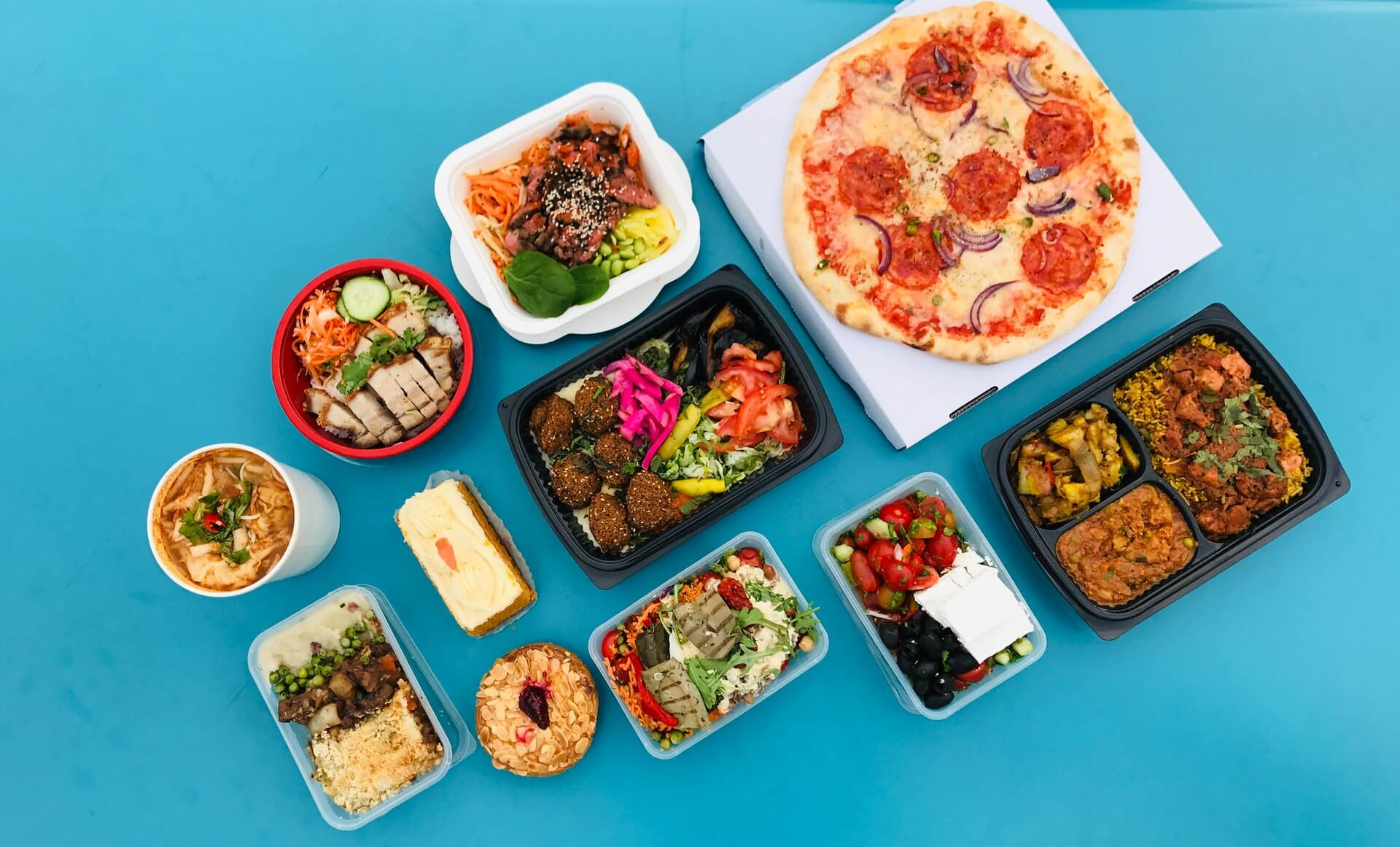 different types of food placed on different containers blue background