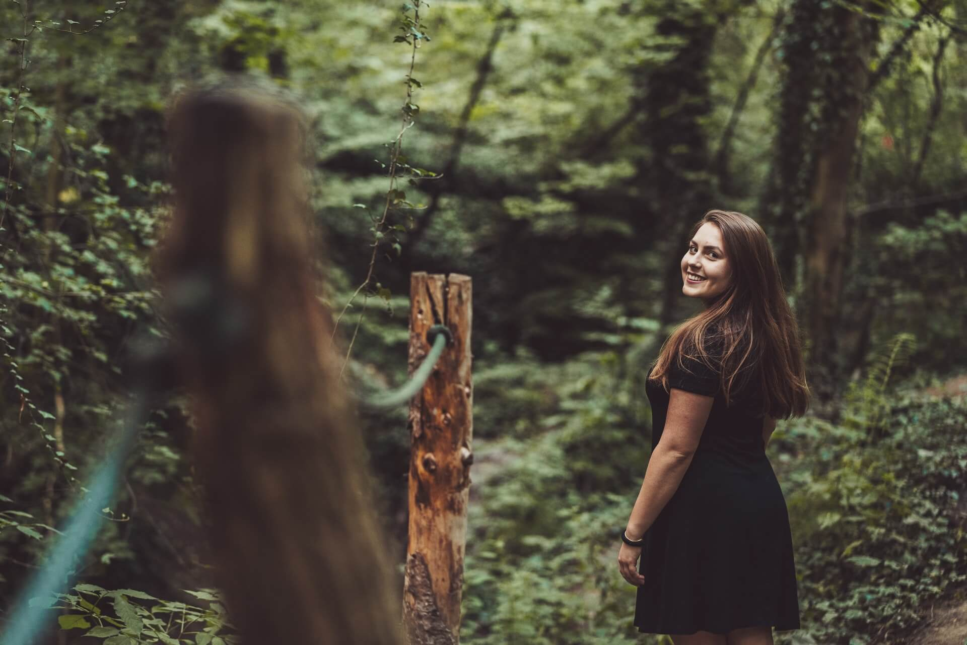 woman in a forest looking back standing beside a post