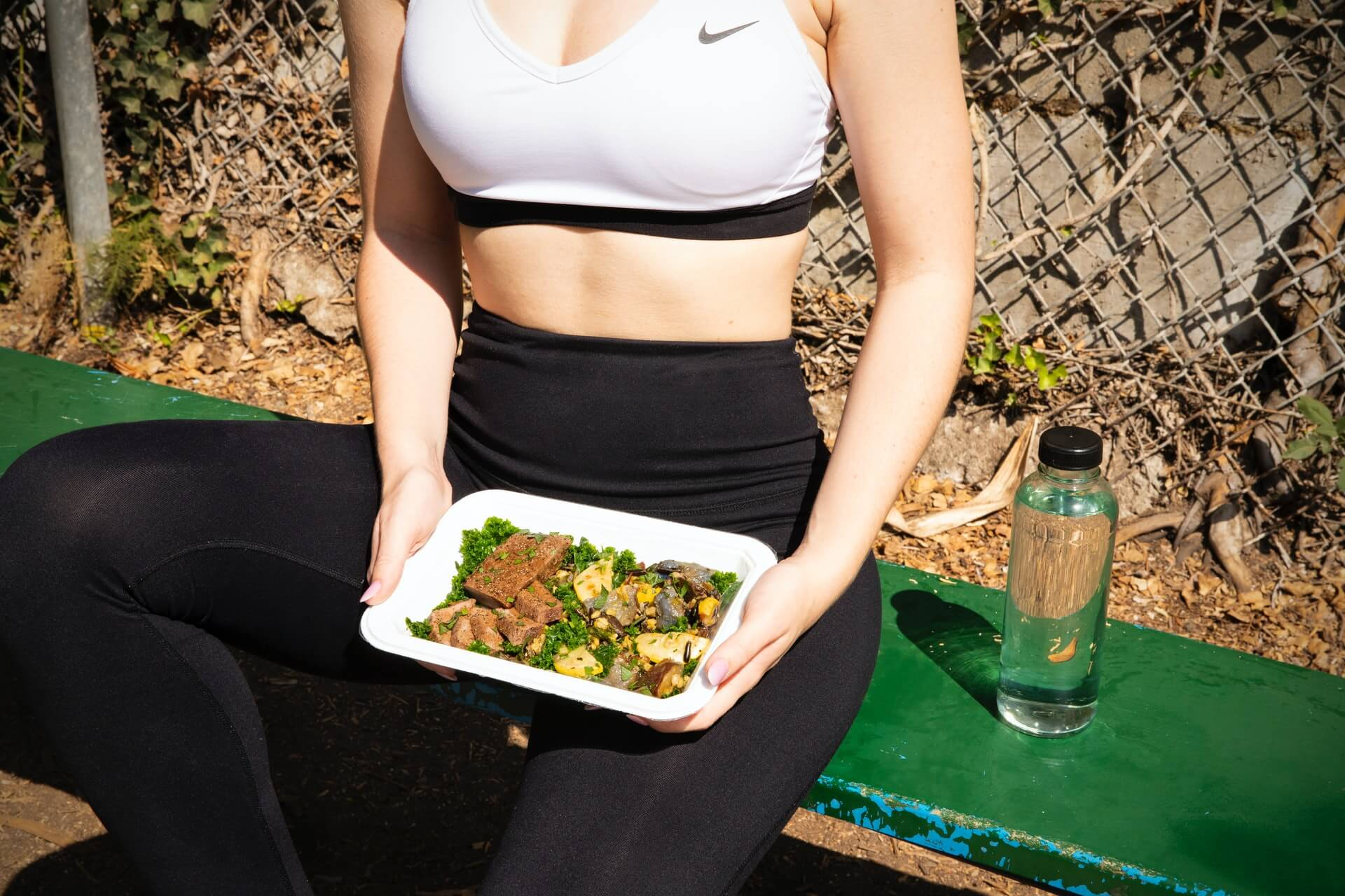 woman wearing athletic attire holding square plate filled with food