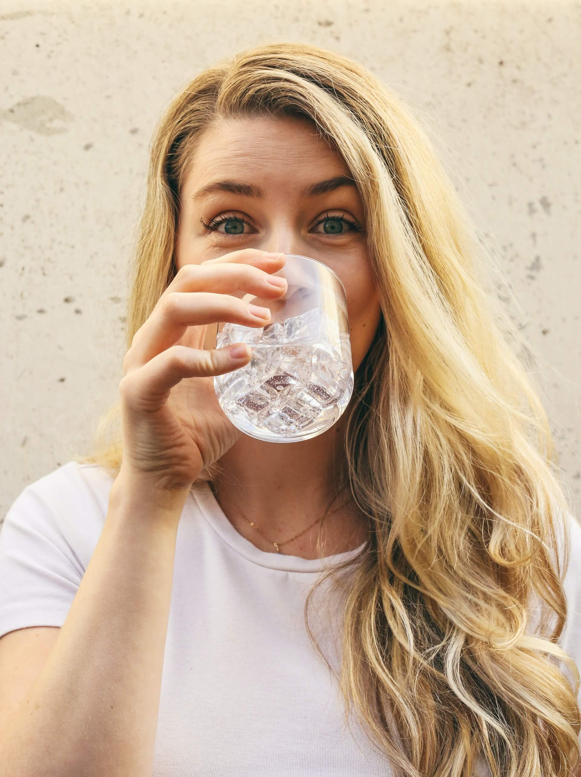 woman blond hair wearing white top drinking water with ice cubes from glass