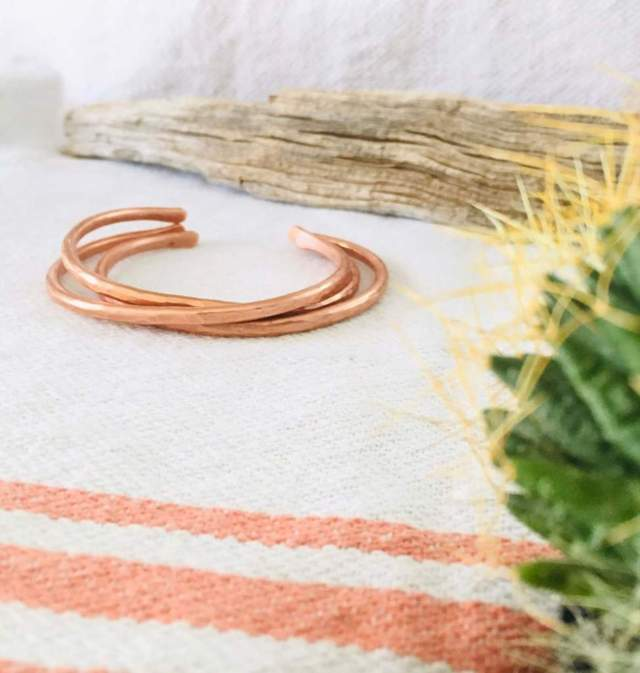three thin stacked copper bracelets placed on a fabric mat