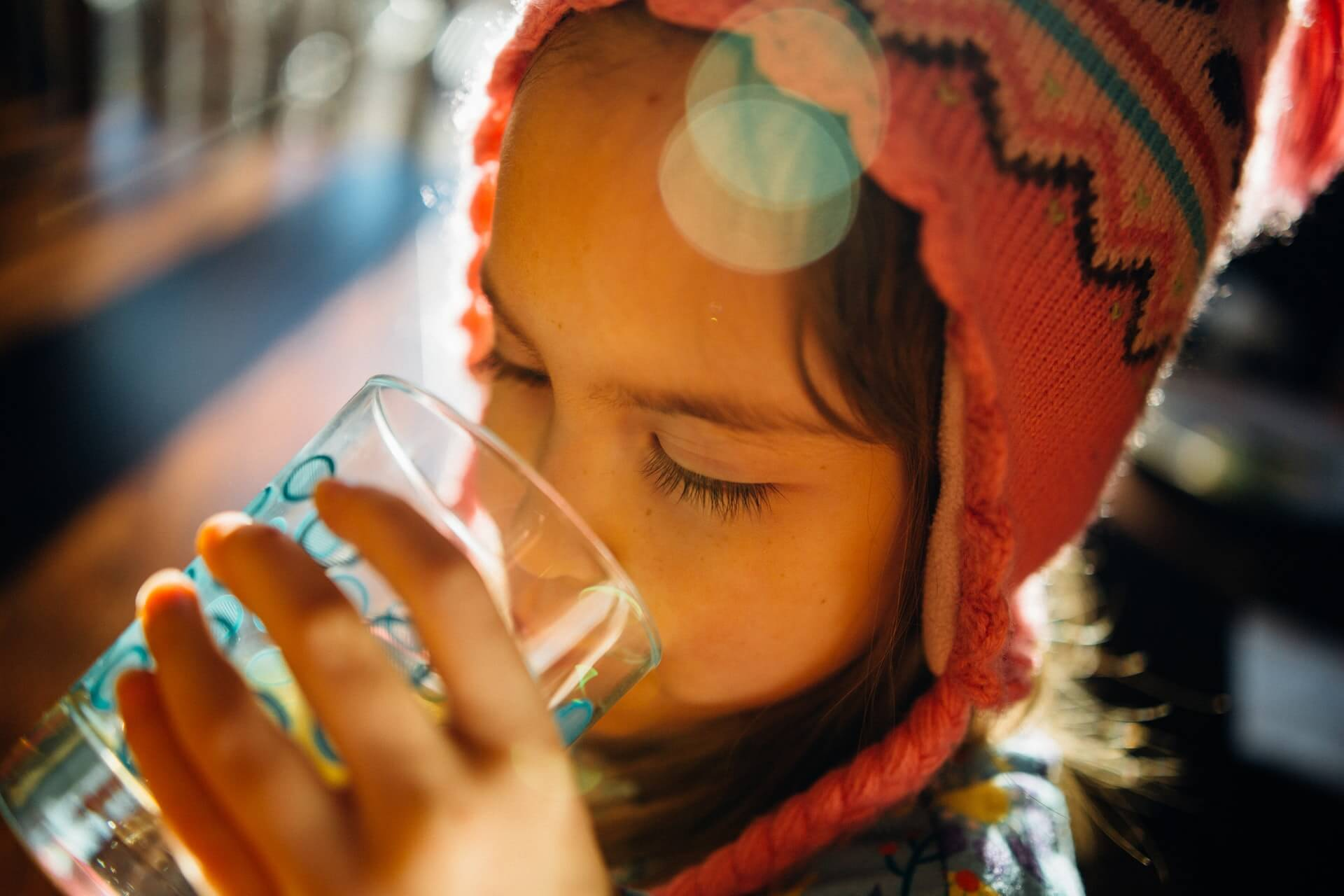 little girl wearing red hat drinking water from a clear glass