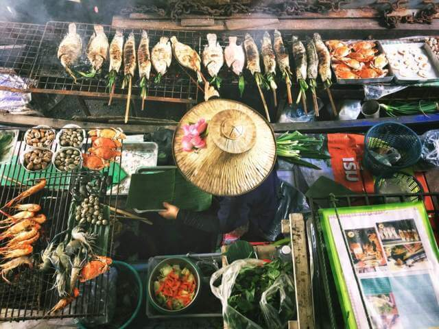 person wearing straw hat surrounded by seafood street food