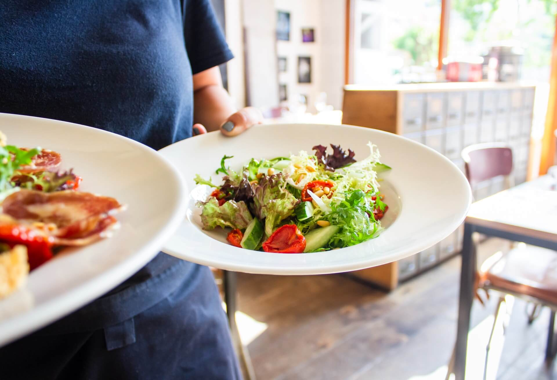 person carrying two round plates filled with vegetables salad