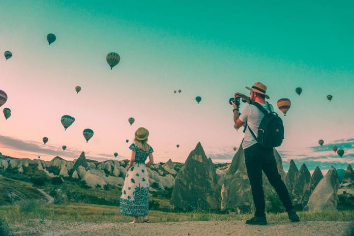 man taking photos woman posing surrounded by hot air balloons in the horizon