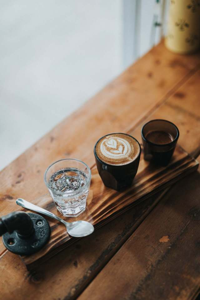 different cups containing water latte coffee spoon placed on a wooden surface