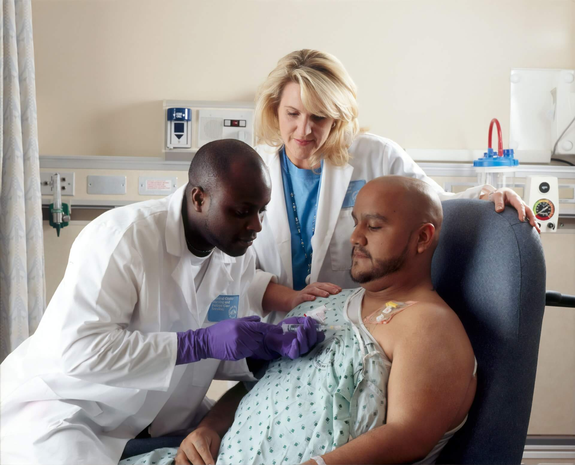 bald man being attended by two doctors in a hospital setting