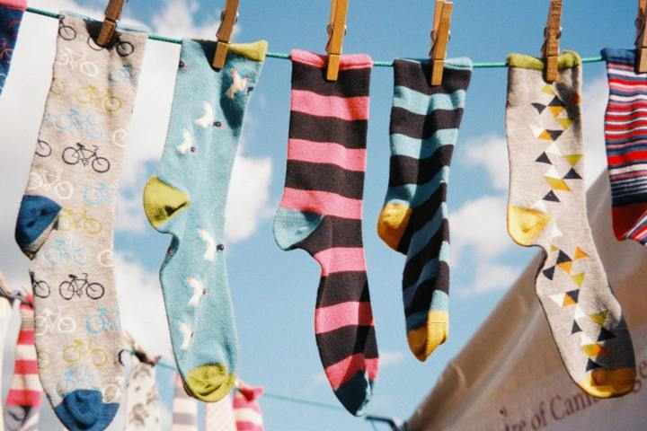 many pieces of socks different colors patterns on a clothes line