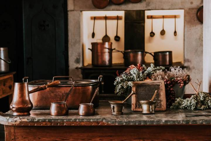 many pieces of different types of copper vessels in a kitchen setting