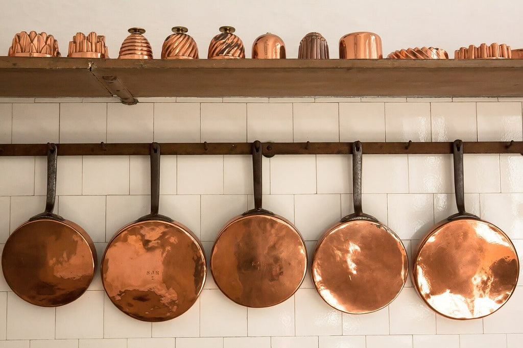 copper cups arranged on a shelf and pans hanged horizontally