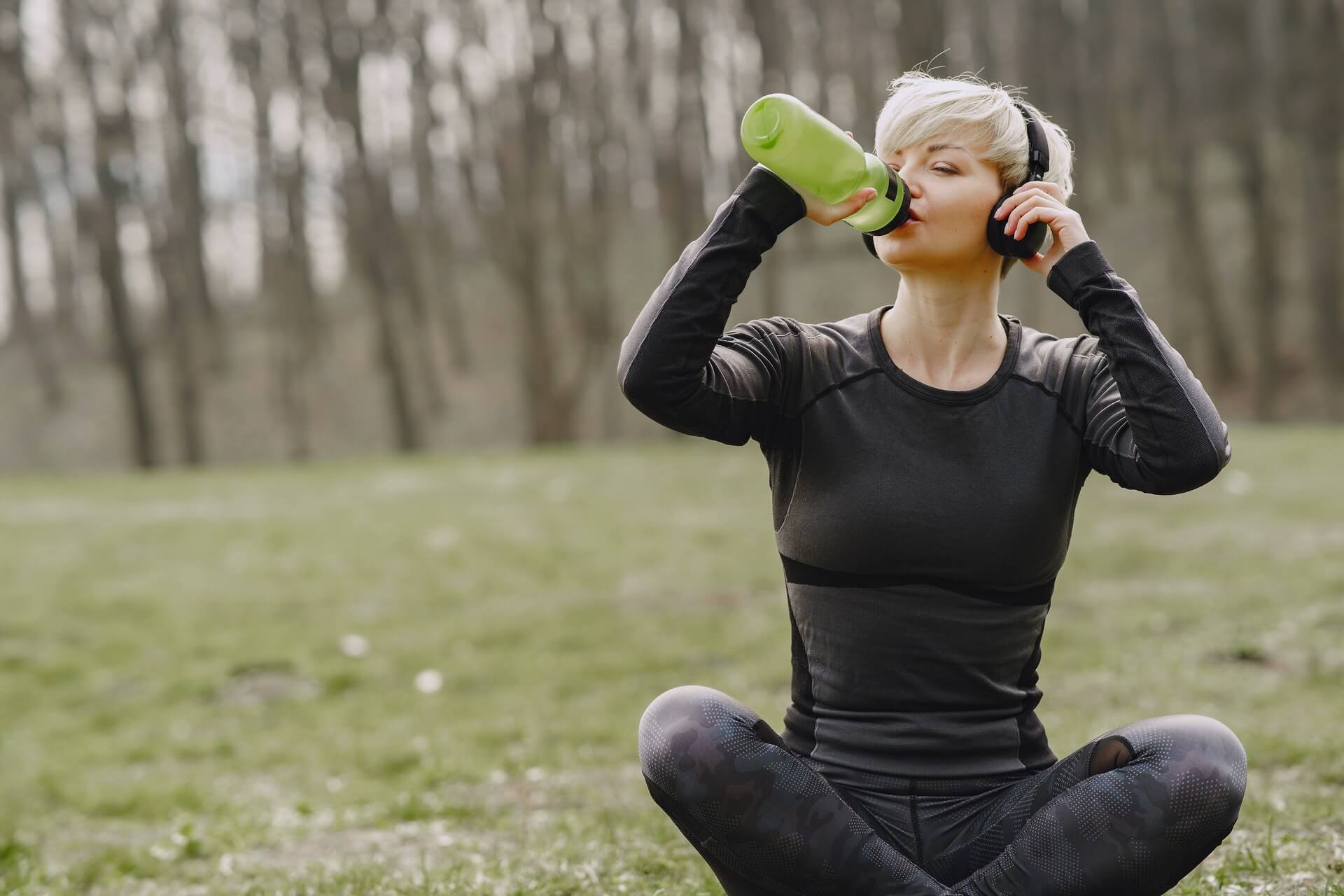 woman with short hair sitting in lotus position wearing headphones drinking from green bottle
