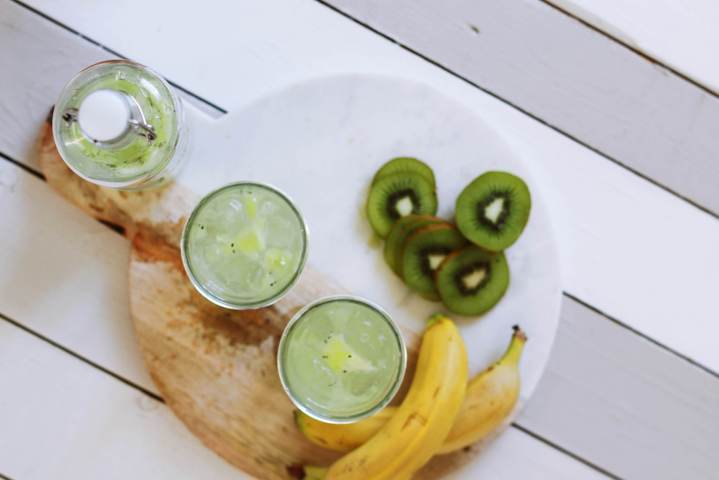 two glasses and bottle filled with water and kiwi slices top view