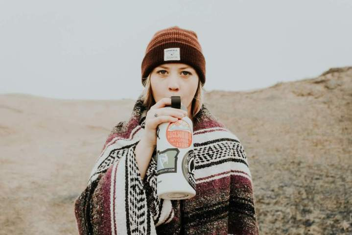 woman middle of the desert facing front sipping from a water bottle