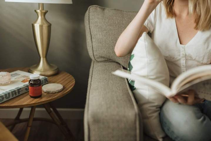 woman sitting on a sofa holding a book coffee table beside