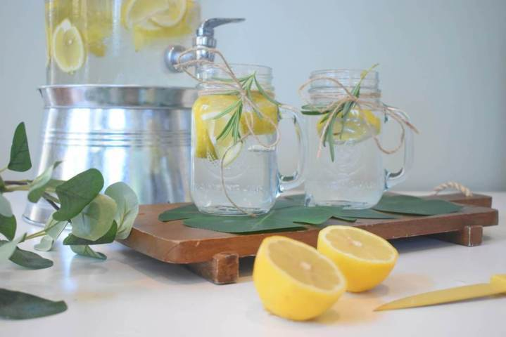 two mason jars filled with water lemon slices placed on a wooden board