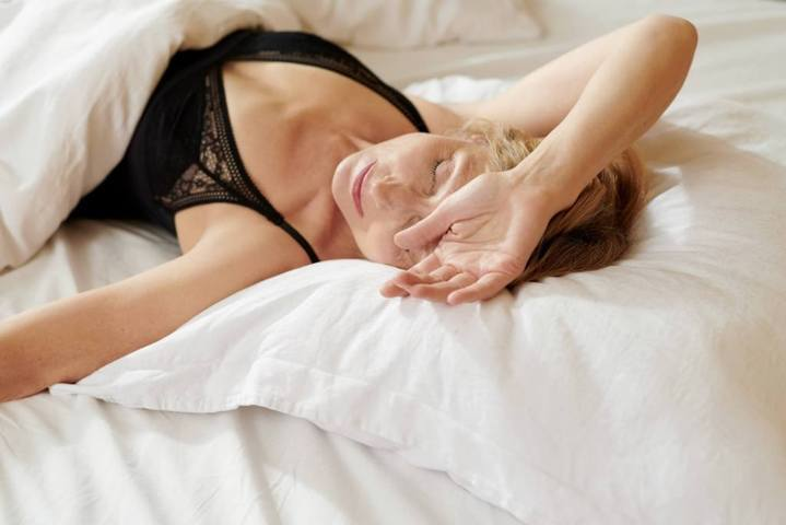 woman wearing black lingerie lying on a white bed