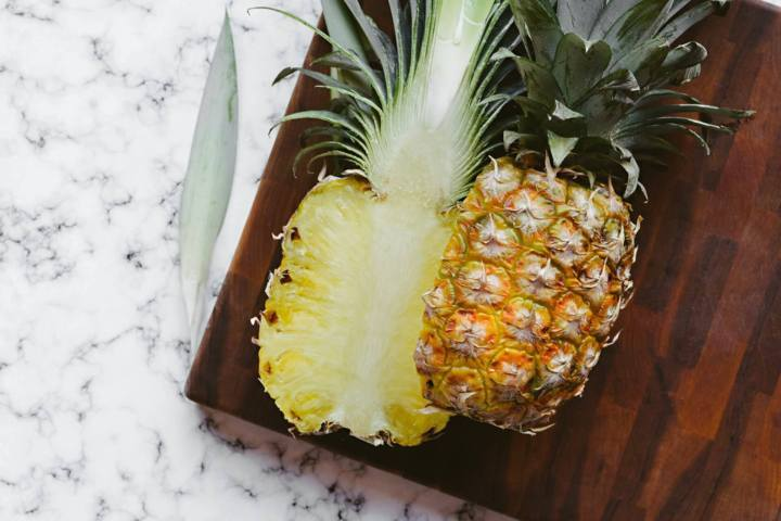 pineapple slice in half placed on a wooden board on a marble surface