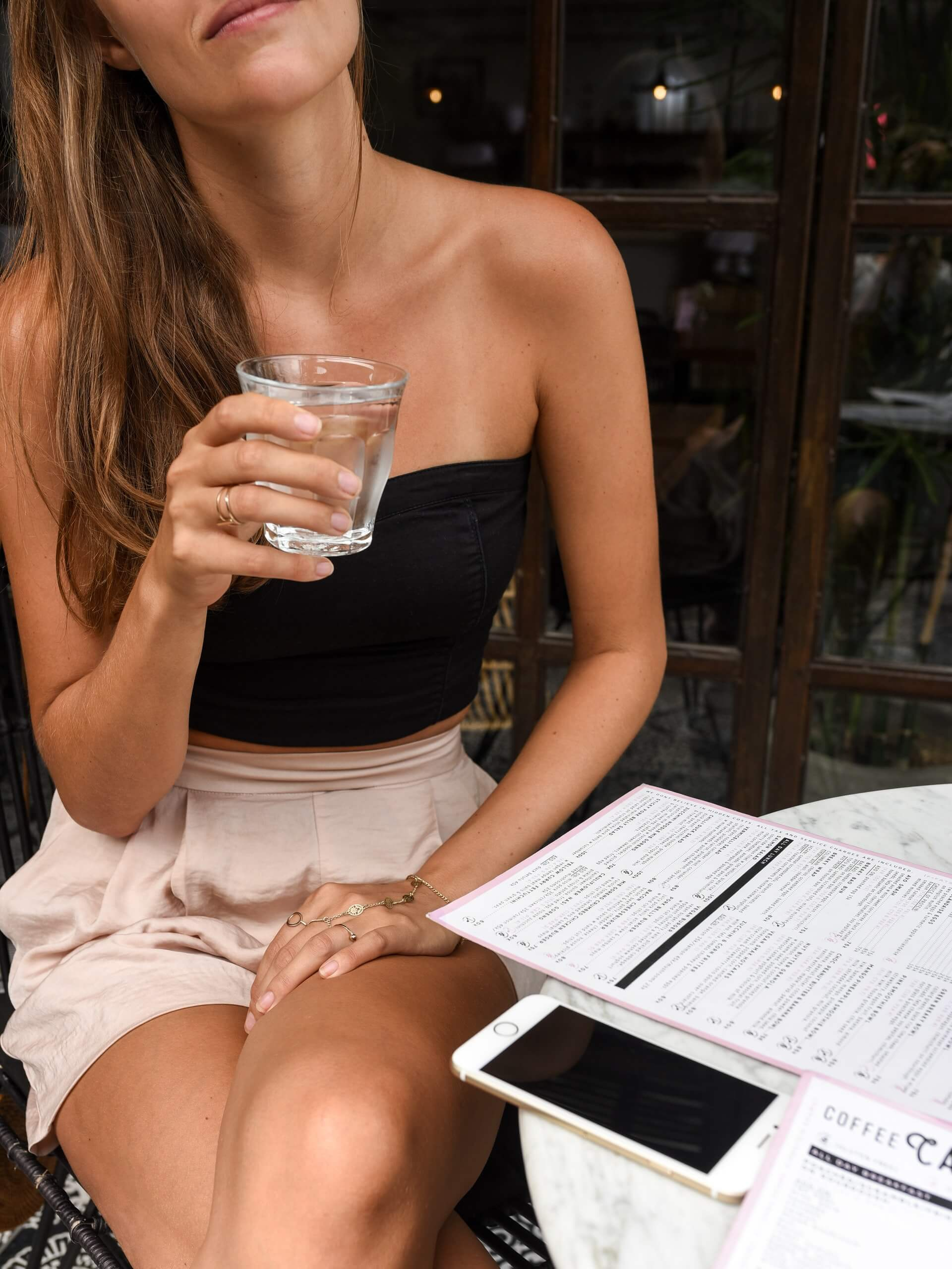 woman wearing black crop top beige shorts holding glass of water
